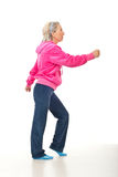 Senior woman workout. In a pink-gray suit over white background Royalty Free Stock Photo