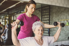 Senior woman workout in rehabilitation center. Senior women workout in rehabilitation center. Personal trainer helping senior woman Stock Image