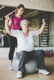 Senior woman workout in rehabilitation center. Senior women workout in rehabilitation center. Personal trainer helping senior woman Stock Photography