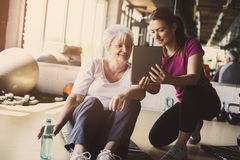 Senior woman workout in rehabilitation center. Senior women workout in rehabilitation center. Personal trainer showing something  on digital tablet Stock Photography