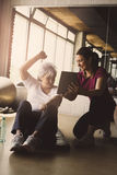 Senior woman workout in rehabilitation center. Senior women workout in rehabilitation center. Personal trainer showing something  on digital tablet Stock Photo