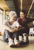 Senior woman workout in rehabilitation center. Senior women workout in rehabilitation center. Personal trainer writing record exercise Royalty Free Stock Photo