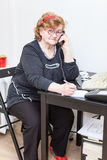 Senior woman at workplace with phone in office Royalty Free Stock Photography