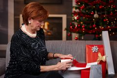 Senior woman wrapping christmas gifts Royalty Free Stock Photos