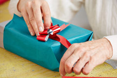 Senior woman wrapping gift with ribbon at christmas Stock Photos