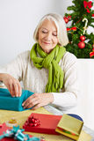 Senior woman wrapping gifts for christmas Royalty Free Stock Image