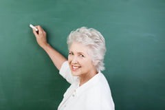 Senior woman writing on a chalkboard. Senior woman writing on a blank chalkboard during a college class or business presentation turning to look back and smile Stock Image