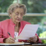 Senior woman writing a check paying bill. Mature woman reading document and writing a check Royalty Free Stock Photo