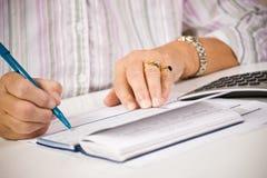 Senior woman writing checks royalty free stock photography