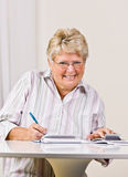 Senior woman writing checks Stock Photo