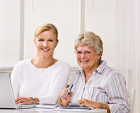 Senior woman writing checks with daughter help Stock Photography