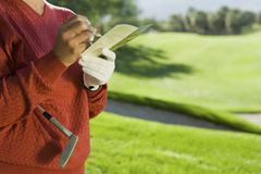 Senior Woman Writing Golf Score. Midsection of a senior women writing golf score on scorecard Royalty Free Stock Photography