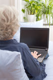 Senior woman writing on laptop Royalty Free Stock Image