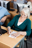 Senior Woman Writing On Notepad In Computer Class Royalty Free Stock Image