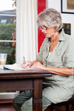 Senior woman writing notes at home Royalty Free Stock Photos