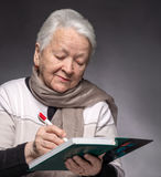 Senior woman writing notes in a notebook Stock Photo