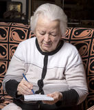 Senior woman writing notes Royalty Free Stock Photo