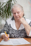 Senior woman writing something. With a pen Royalty Free Stock Photo