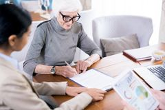 Senior woman writing testament. Senior woman wearing eyeglases writing testament with notary agent sitting near by her stock image