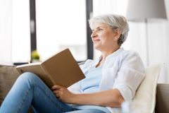 Senior woman writing to notebook or diary at home stock images