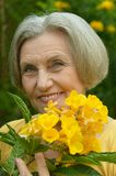 Senior woman with yellow flowers Royalty Free Stock Image