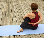 Senior woman yoga. Senior woman doing yoga on a deck floor Royalty Free Stock Image