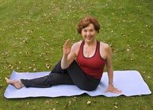 Senior woman yoga. Senior woman doing yoga on the grass Royalty Free Stock Image