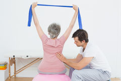 Senior woman on yoga ball with a physical therapist Stock Photography