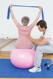 Senior woman on yoga ball with a physical therapist Royalty Free Stock Image