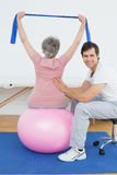 Senior woman on yoga ball with a physical therapist Royalty Free Stock Photography