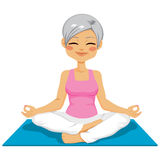 Senior Woman Yoga. Mature senior woman practicing zen position on yoga mat isolated on white background Stock Photo
