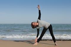 Mature woman yoga triangle on the beach. Mature woman doing triangle yoga pose on the beach Royalty Free Stock Image