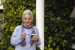 Senior woman with yogurt. A senior woman eating a yogurt Royalty Free Stock Photos
