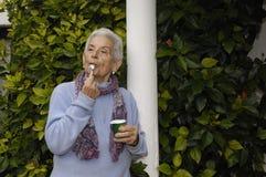 Senior woman with yogurt. A senior woman eating a yogurt Stock Photo