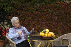 Senior woman with yogurt. A senior woman eating a yogurt Royalty Free Stock Images