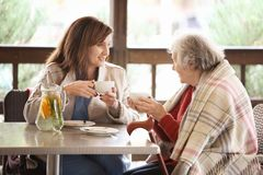 Senior woman and young caregiver drinking tea at table. Senior women and young caregiver drinking tea at table in cafe royalty free stock photo