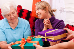 Senior woman and young female gets presents Stock Image
