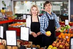 Senior woman and young man offering seasonal fruits Royalty Free Stock Photos