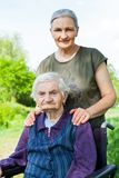 Elderly care. Senior women with alzheimer disease sitting in wheelchair, posing with her daughter in the park Stock Photos