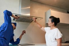 Repairing extractor hood. Senior women asking repairman to check extractor hood Royalty Free Stock Image