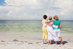 Senior women on beach. Back view of three senior women friends looking out at ocean stock photo