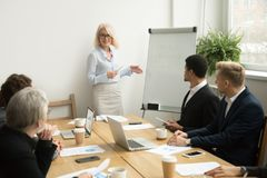 Senior woman boss leading corporate team meeting or giving prese. Senior women boss leading corporate team meeting presenting team goals, smiling aged stock photo