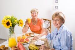 Senior women breakfast. Happy senior women having breakfast together at home Stock Photos