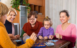 Senior women with child at desk with bingo. Senior female friends with child sitting at desk with bingo. Focus on girl Royalty Free Stock Photos