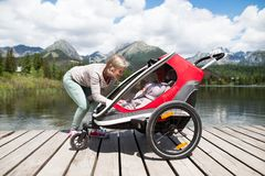 Senior woman and children in jogging stroller, summer day. Senior women and children in jogging stroller at he lake, summer day. High mountains in the Stock Photos
