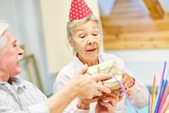 Senior woman with dementia gets a gift stock photography