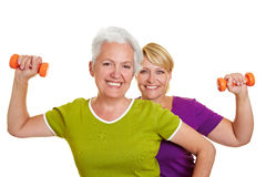 Senior women doing fitness training. Two happy senior women doing fitness training with dumbbells Stock Photography