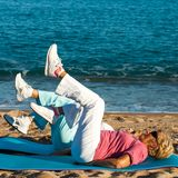 Senior women doing leg exercises on beach. Stock Images