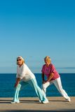 Senior women doing stretching exercise at seafront. Stock Photo