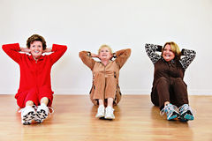 Senior women exercise class. Three smiling senior women doing sit ups in a row in an exercise class stock photos